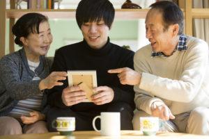 故人の遺品としての写真を見ている家族