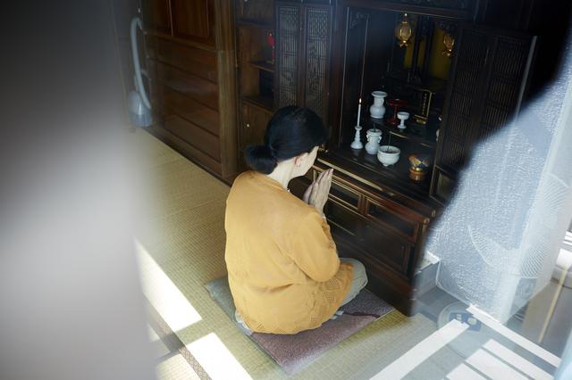 仏壇にてを合わせる女性
