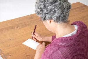 終活年賀状を書く女性